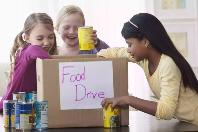 Fetele care plasează cutii de hrana în cutie de donare