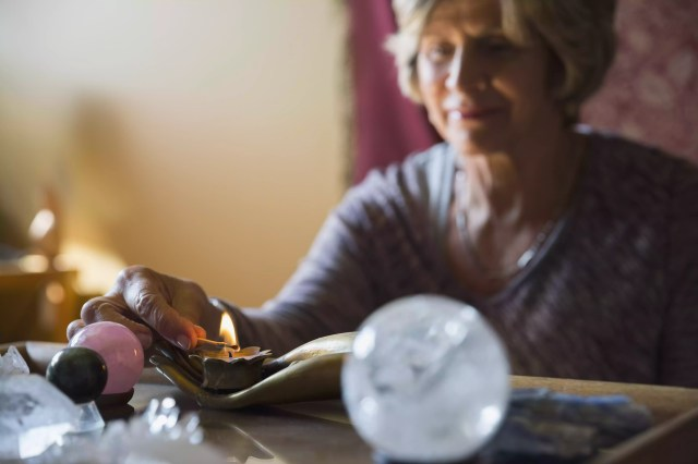 Senior femeie lumina lumânare pentru meditație