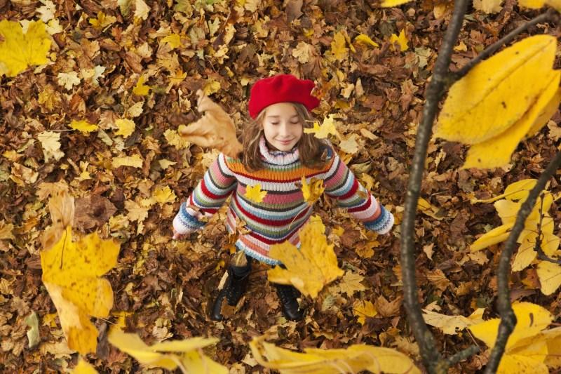 Fille debout dans le feuillage d'automne