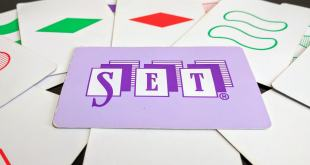 Several set cards arranged on a table with one card featuring the word Set prominently