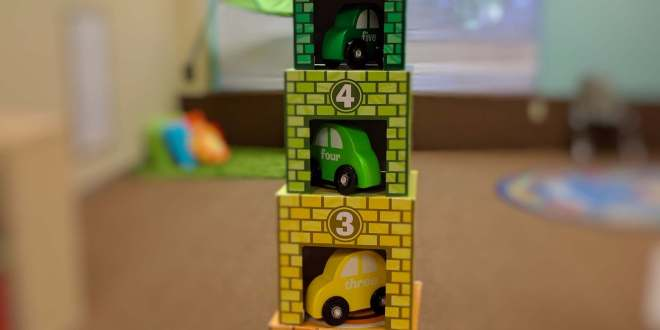 Stack of toy cardboard garages with wooden cars inside