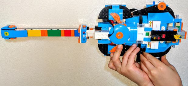 boy's hands holding a LEGO guitar made from the LEGO Boost set