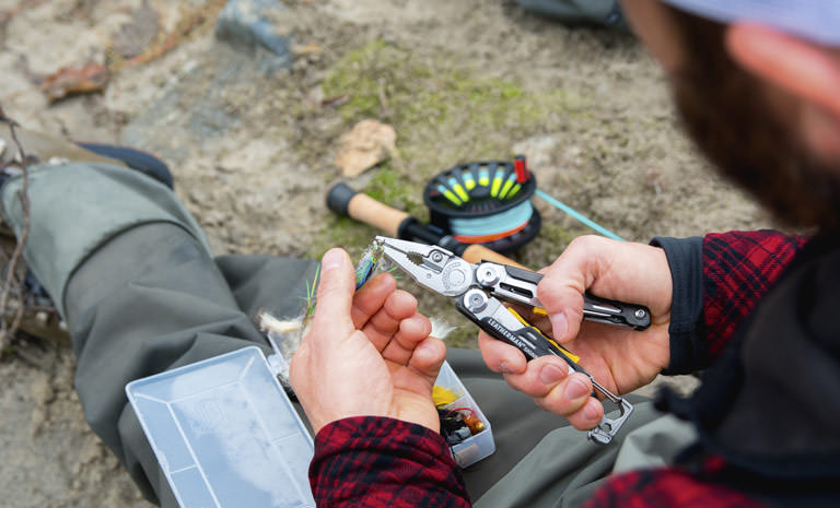 leatherman signal multi-tool in hand, man using plier tool
