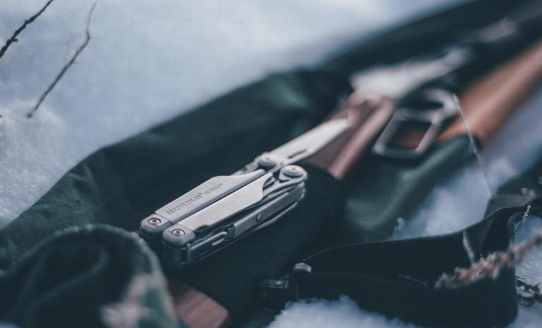 Leatherman stainless steel surge multi-tool on hunting gun