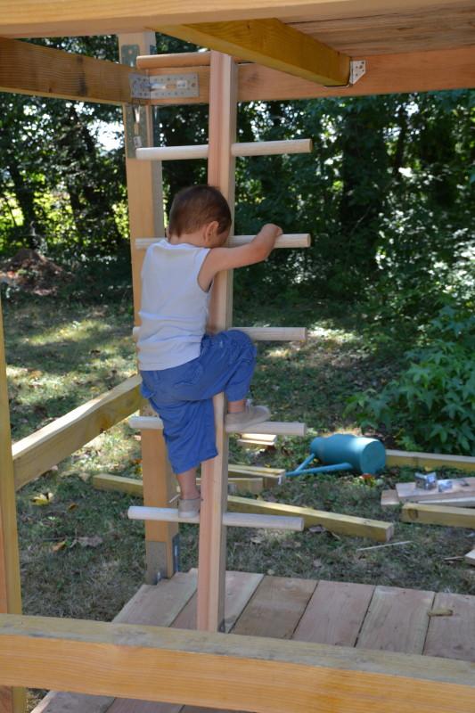 Enfant escaladant la tour médiévale en construction