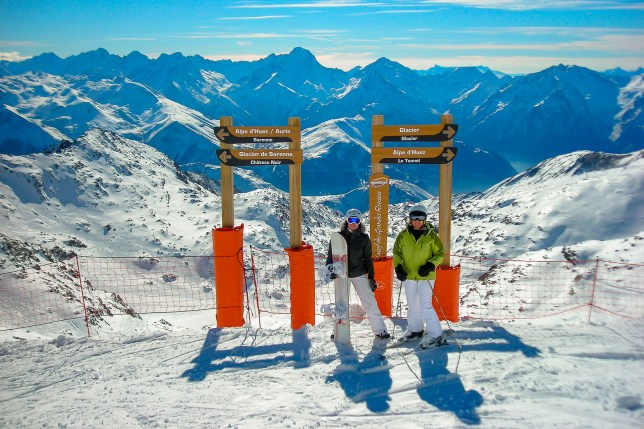 ski and snowboarder on piste in Alpe d'Huez with snowy French Alps