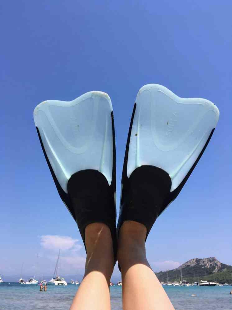 Palmes de plongées sur ciel bleu et vagues turquoises.