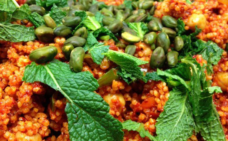 Gewürzhirse Taboulé mit Frühlingszwiebeln, Kichererbsen, Rosinen, getrockneten Tomaten, Pistazien und Minze