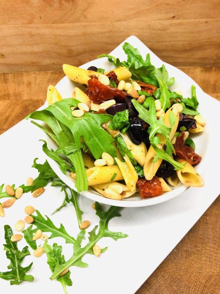 Nudelsalat mit Tomaten, Oliven, Rucola und Pinienkernen