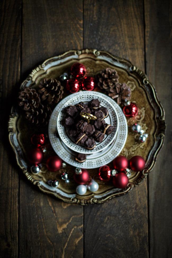 Nougat Tuffs auf Florentiner Tablett mit roten Christbaumkulgeln und weißem Porzellanteller.