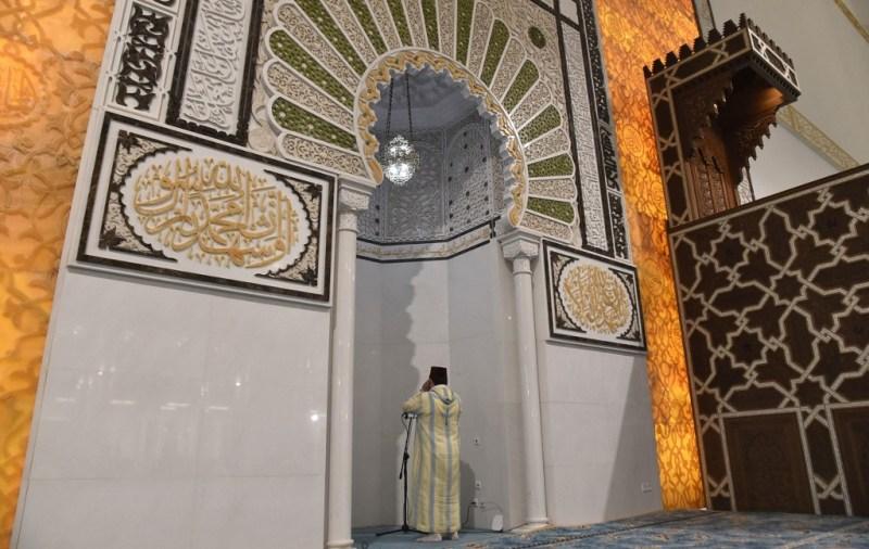 La grande mosquée d'Alger : Un imam menant une prière devant le mihrab niche indiquant la direction de la Kaâba.