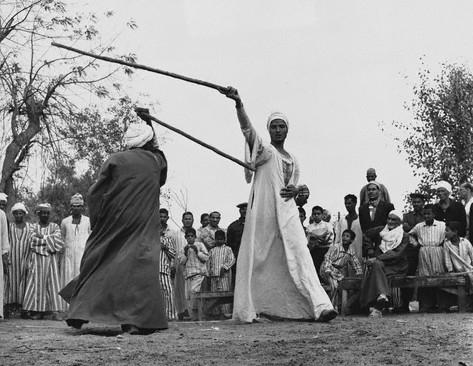 Due uomini eseguono la danza folcloristica con il bastone - 1966, Cairo, Egypt - Image by © Hulton-Deutsch Collection/CORBIS