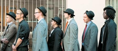 Ces jeunes chômeurs portent un habit veston ainsi qu'un chapeau rond mal placé sur leur tête