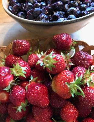 Last frozen blueberries, fresh picked strawberries