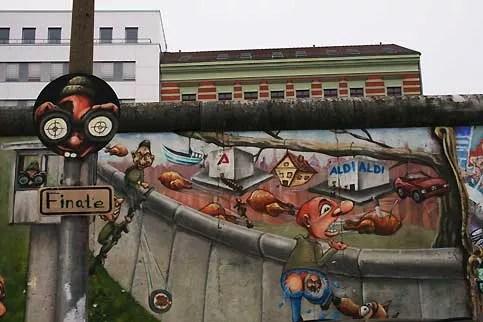 Les artistes ont aussi investi le côté ouest du mur. Avant la chute du rideau de béton, la plupart des Allemands de l'Est (Ossis) devaient se contenter de fantasmes sur la vie chez leurs voisins occidentaux, perçue comme un paradis de la consommation, avec ses supermarchés regorgeant de victuailles et ses voitures de luxe. De nombreux Ossis ont bravé les gardes frontières est-allemand, au péril de leur vie, pour fuir la dictature communiste et passer de l'autre côté, pour y vivre en liberté. Ici, les personnages de la fresque, peinte sur la face ouest, fuient involontairement, ou non, vers l'ancien Berlin Est… aujourd'hui totalement occidentalisé. Depuis le début de la crise financière, une majorité d'Ossis estiment, qu'ils vivent une sorte de plongée cauchemardesque dans l'enfer capitaliste.
