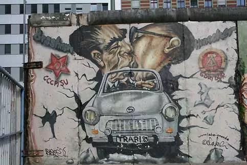 Embarqués dans une trabi, le patron de l'URSS, Leonid Brejnev, et son protégé est-allemand, Erich Honecker, traversent le mur qu'ils ont érigé ensemble. La célèbre photographie du «baiser de la honte» symbolisera la domination soviétique sur la RDA et donnera lieu à de nombreuses illustrations. Usée par le temps, la plus célèbre fresque s'est presque totalement effacée.