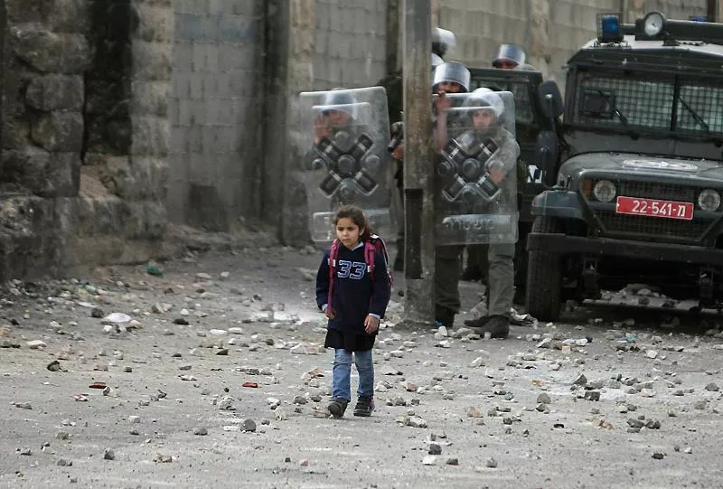 Le visage fermé, le regard concentré, cette petite fille palestinienne sur le chemin de l'école passe lentement un barrage de la police des frontières israélienne. La peur au ventre, elle fait tout pour ne pas regarder le drame qui se joue. Une scène terrible. Tant par sa banalité que par ce qu'elle ne montre pas. En effet, au moment même où la jeune écolière passe devant les policiers, des émeutiers palestiniens du camp de Chouafat lancent des pierres dans leur direction. L'affrontement tourne vite à l'émeute et la violence monte. Puis tout s'arrête pour laisser passer l'enfant. Un instant suspendu dans le terrible conflit israélo-palestinien.