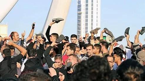 Des manifestants anti-gouvernementaux brandissent leurs chaussures en signe de protestation, le 15 février 2011 à Manama, Bahreïn.