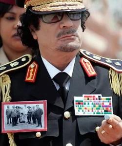 Mouammar Kadhafi en juin 2009 devant la garde d'honneur italienne après avoir atterri à Rome. Sur sa veste, une photo d'Omar Mukhtar (enchaîné), résistant libyen contre la colonisation italienne, arrêté et exécuté en 1931. Crédits photo : AP