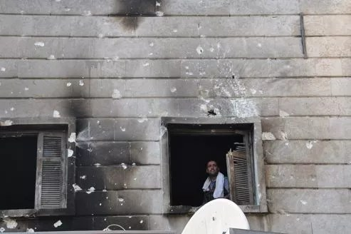 Un volontaire de l'ASL à la fenêtre du commissariat d'al-Shaar, à Alep, dont la facade porte les stigmates de combats.