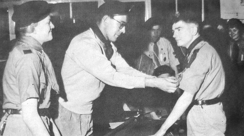 Scoutmaster C. Rand pins the First Class Badge on the tunic of 17 year old Richard Paton, the first member of the 2nd Swansea (Grove) Troop the get the award.