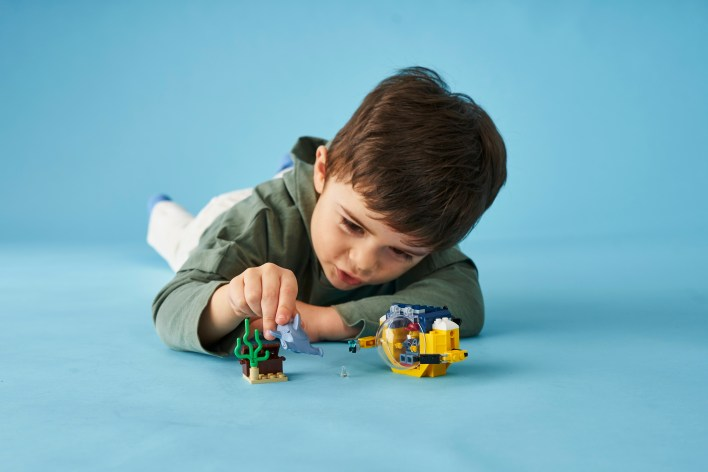 Young boy lying on the floor and playing with an underwater scene made of LEGO bricks