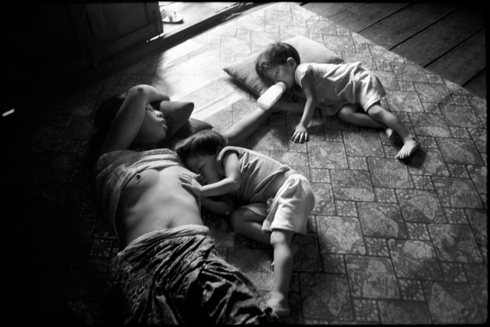 A woman looks after her children on the floor of a dilapidated house. A bit of light falls through the broken window panes