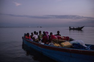 SEBAGORO, UGANDA - MARCH 23: A boat filled with Congolese refugees lands at Sebagoro, Uganda on March 23, 2018. The journey from Ituri can take three to 10 hours, depending on the quality of the boatÕs motor, and most who arrive have not eaten for days having spent multiple nights sleeping in IturiÕs dense forest. Violence in Ituri Province in northeastern Democratic Republic of Congo has displaced more than 400,000 people including approximately 40,000 refugees who have fled to Uganda.