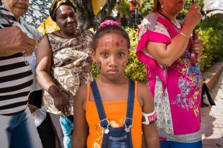 "A Cuban child waiting for the funeral procession carrying the ashes of Fidel Castro to their final destination: the cemetery of Santa Ifigenia in Santiago de Cuba, 4 December 2016. The girl has the revolutionary slogan ""Yo soy Fidel"" (I'm Fidel) painted on her cheek, while her arm bares a typical armband of the ""26th of July Movement"", the day when Moncada was conquered. The ""26th of July Movement"" was a vanguard revolutionary organization led by Fidel Castro that overthrew the Fulgencio Batista dictatorship in 1959."