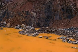 Basalt mine in the Tamatave region. Laterite soil gives the water its orange color.