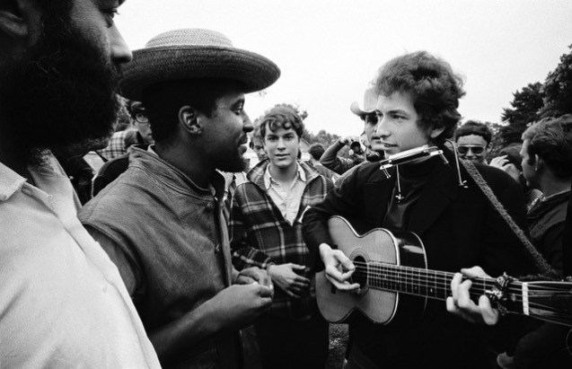 "Newport Folk Festival 1964. Bob Dylan & Len Chandler. Len was a classically trained musician with an MA from Columbia University and in the early 60s got involved in the Civil Rights Movement. One of his songs, "" Keep on keeping' on"" was used in a speech by Martin Luther King Jr. in 1964. © Jim Marshall Photography LLC"