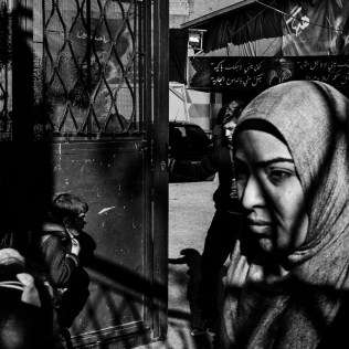 A veiled woman walks out of the yard of El Ahliyah school with her daughter after picking her up from school