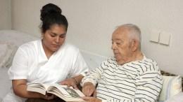 Infirmière aidant un homme âgé à lire