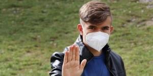 adolescent masqué montrant sa main
