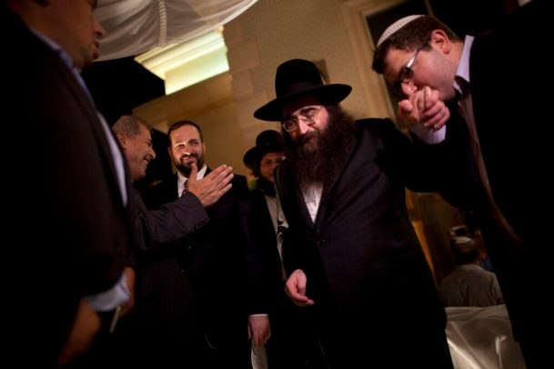 In this July 11, 2011 file photo, a man kisses the hand of Rabbi Yoshiyahu Pinto at a wedding in Lod, central Israel.  In the fall of 2009, when future U.S. Rep. Michael Grimm announced his run for congress, he sorely needed a rainmaker who could get the dollars flowing to his nascent campaign. He found one in an Israeli Rabbi Pinto, but now that fruitful association has turned into a big headache for the Staten Island Republican - one involving allegations of illegal donations, a bizarre blackmail claim and potentially embarrassing associations with people in the pornography business. (AP Photo/Oded Balilty, File)