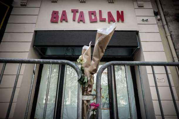 """Flowers are tied to a fence outside the """"Bataclan"""" concert hall during All Saints' day in Paris on November 1, 2016, one of the targets of the November 13, 2015 terrorist attacks during which 130 people were killed and another 413 were wounded in the French capital. / AFP PHOTO / PHILIPPE LOPEZ"""