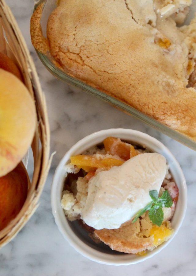 Ramekin of fresh peach cobbler with vanilla ice cream