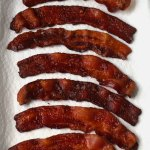 View of crispy and golden brown perfectly cooked bacon laying on a paper towel lined tray