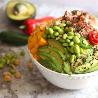 This Ahi Tuna Poke Bowl recipe is so easy to make at home! Light, fresh, healthy and delicious! Loaded with fresh Ahi Tuna with citrus ponzu sauce, rice, cucumbers, avocado, edamame and mango. Drizzled with creamy sriracha sauce and topped with crunchy nuts. This Ahi Poke bowl is amazing!