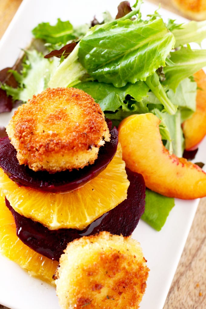 Close up view of a stack of sliced beets and oranges topped with a crispy goat cheese coin next to salad greens and sliced peaches.