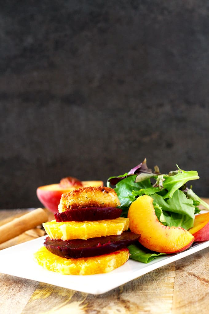A white plate with roasted beets and orange slices next to salad greens and a peach slice/ On the background a peach cut in half and cinnamon sticks .