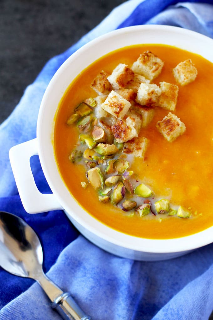 Carrot soup topped with pistachios and croutons in a white soup pot