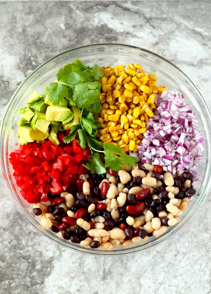 In this photo a glass bowl filled with the ingredients to make this Mexican Three Bean Salad recipe. Beans, Onions, red bell peppers, roasted corn, avocado, cilantro.