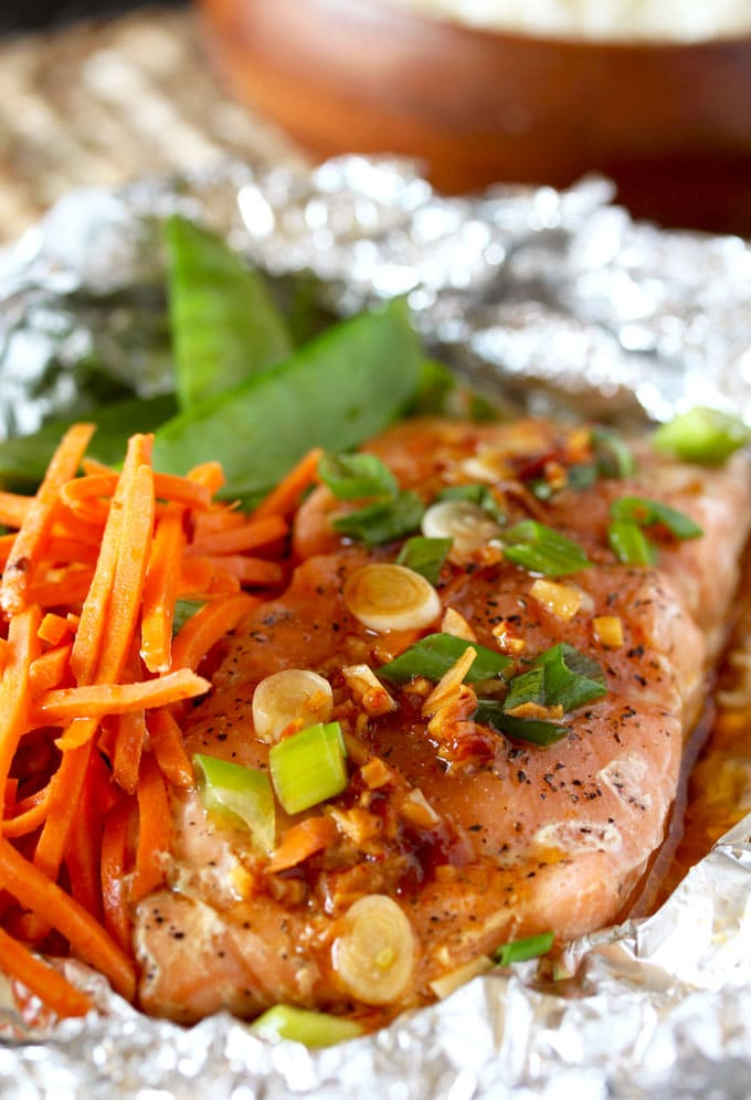 A foil packet opened showing a filet of salmon with Asian Butter with sliced green onions and shredded carrots