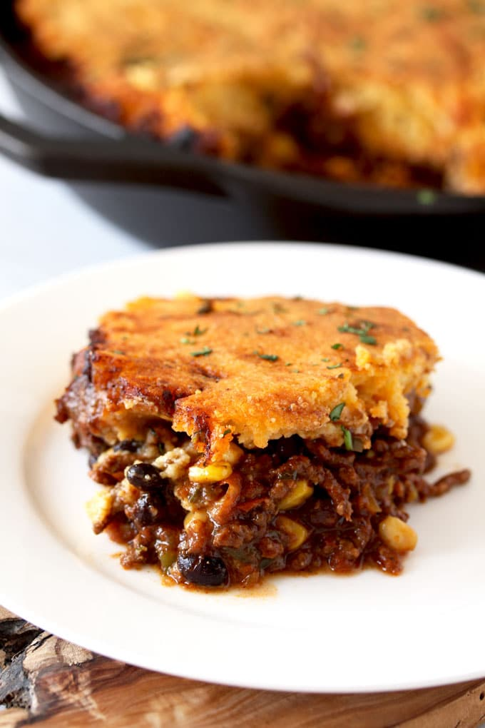 Closed up view of a serving of cornbread tamale pie. You can see both layers, the chili mixture of seasoned beef, corn and beans and the topping. The cornbread topping is golden with brown bits on the ages. Plated on a white plate, sitting next to a cast iron skillet filled with the rest of the cornbread tamale pie.