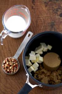 Top view of ingredients to make the caramel-pecan sitting on a wooden surface. In a pot brown sugar and butter cubes. Next to it a measuring cup with chopped pecans. Next to it a liquid measuring cup with cream.