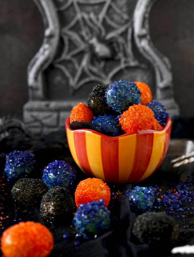 View of a candy bowl filled with sugared covered grapes. The sugared grapes are orange, purple and black. Sitting on a black surface.