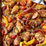 View of seasoned and cooked chicken tenders, sliced red onions, sliced yellow bell peppers, and cherry tomatoes mixed on a sheet pan.