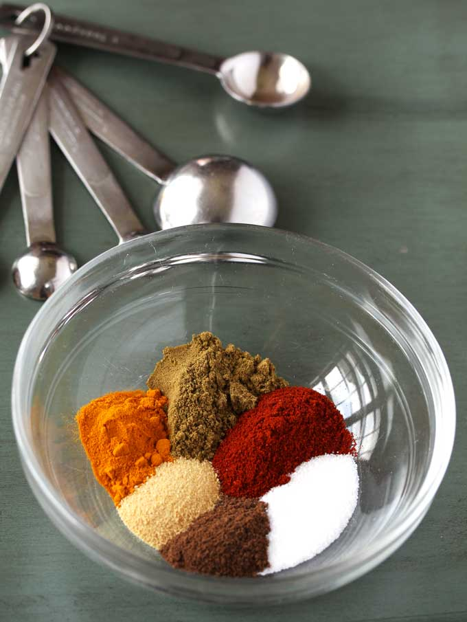A small bowl with ground spices, cumin, paprika, salt, garlic powder, allspice and turmeric and a set of measuring spoons set on a wooden teal surface