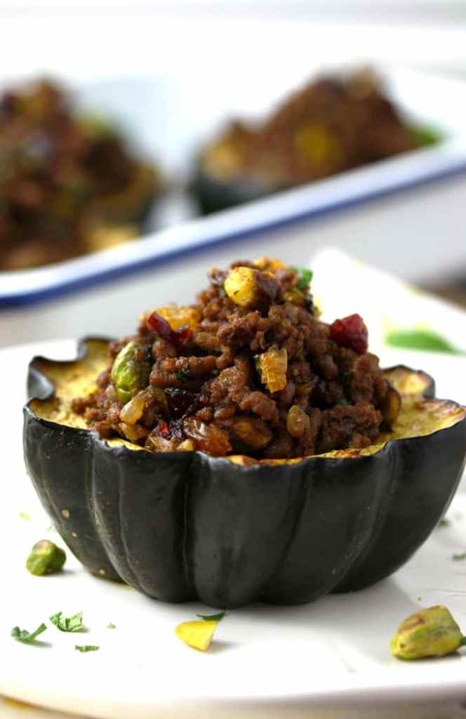 Side view of a stuffed acorn squash with ground beef, pistachios, dried cranberries, golden raisins, chopped parsley and mint on a white plate.